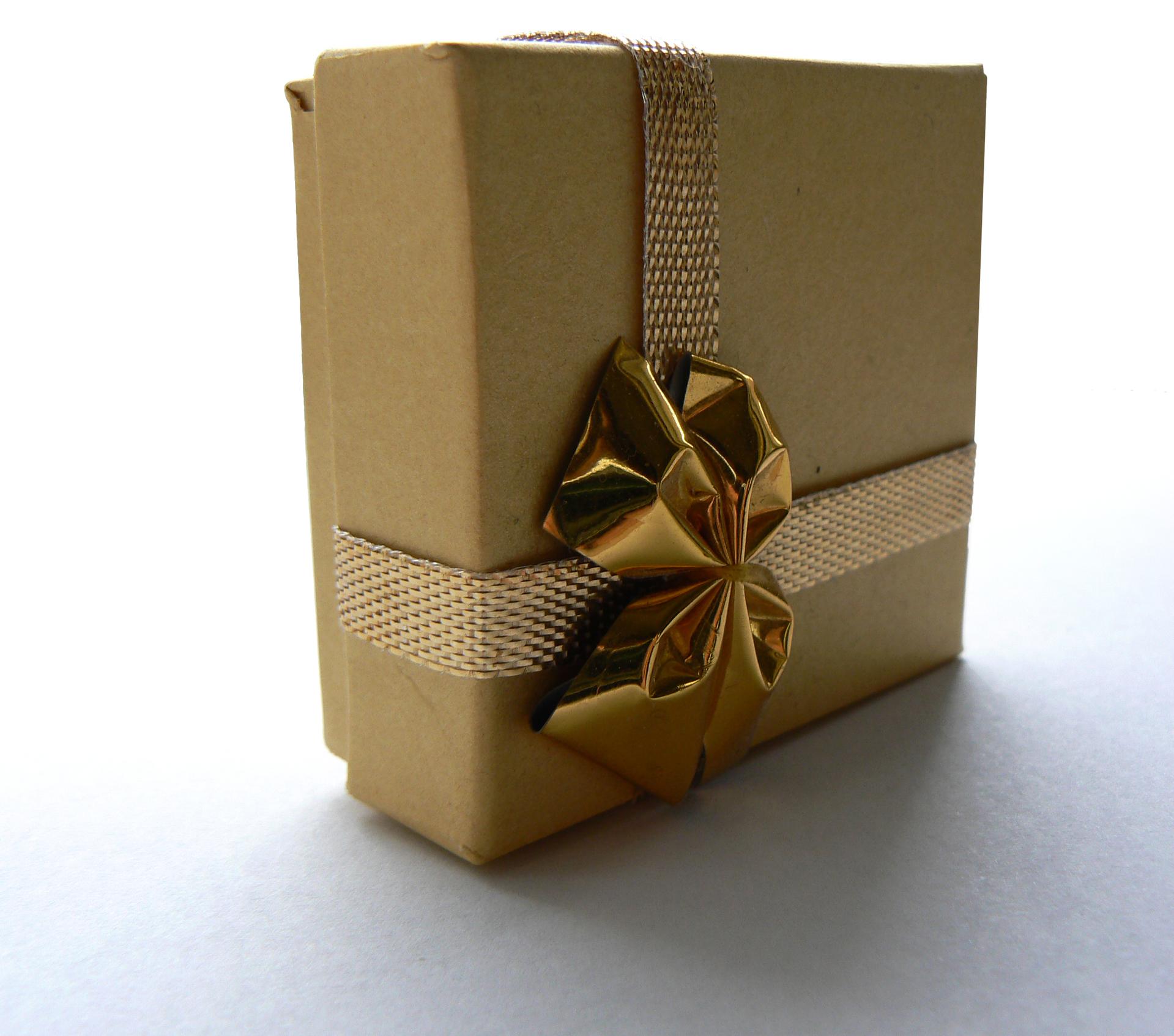 Embalagem quadrada de presente cor kraft com fita dourada.