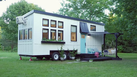 Tiny house branca com deck.