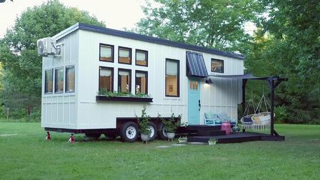 Tiny house branca com deck.